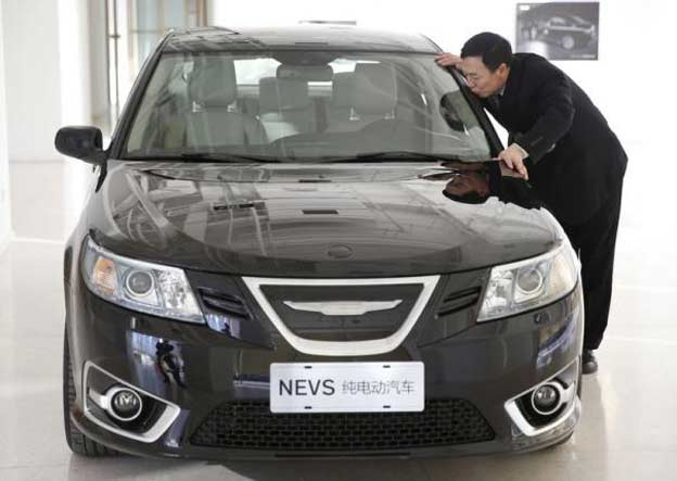 National Electric Vehicle Sweden (NEVS) chairman Jiang Dalong kisses an NEVS electric car as he poses during an interview at its Beijing headquarters building December