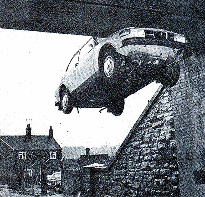 Saab 99 hanging on railway bridge