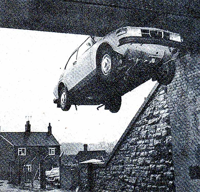 Saab 99 hanging on railway bridge